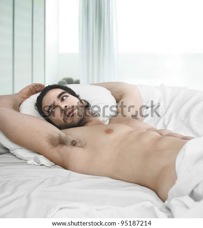 Portrait of a naked man in bed with window behind him - stock photo