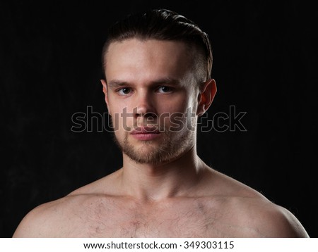 Portrait of a naked muscular man, dark gray background