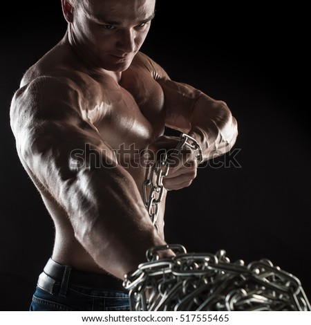 Portrait of a naked torso brutal male bodybuilder athlete holding a chain on a black background