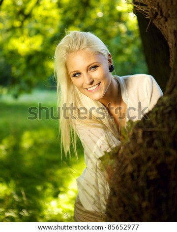 Portrait of a natural and cute female hiding behind a tree in a park. - stock photo