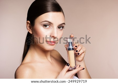 Portrait of a naturally beautiful woman is holding foundation tube that makes skin flawless and perfect - stock photo
