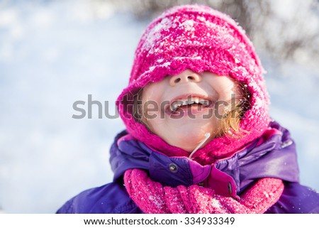 portrait of a naughty little girl playing on snow in winter - stock photo