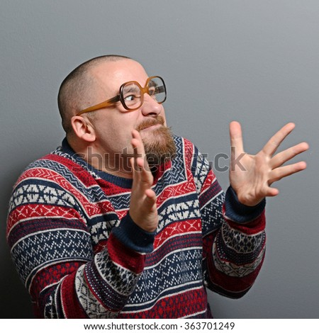 Portrait of a nerd clapping hands with glasses and retro sweater against gray background - stock photo