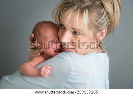 portrait of a newborn baby boy in his mother's shoulder - stock photo