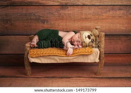 Portrait of a newborn baby boy wearing crocheted green overalls and bear hat. He is sleeping on a miniature wooden bed. Shot in the studio on a rustic wood background. - stock photo