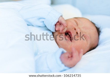 Portrait of a newborn baby crying. - stock photo