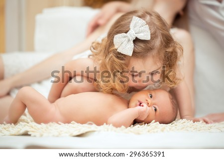 Portrait of a newborn baby with  being kissed by big sister - stock photo
