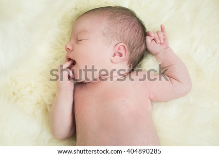 Portrait of a newborn caucasian girl lying on a white blanket - stock photo
