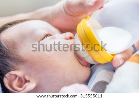 Portrait of a newborn drinking milk from a baby bottle  - stock photo