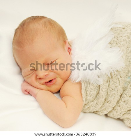 portrait of a newborn sleeping baby making almost crying sad face wearibg white angel wings wrapped in a woolen blanket isolated on white