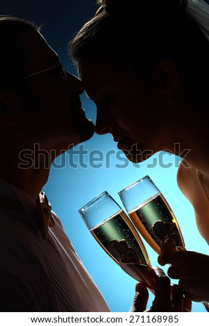 portrait of a newly-married couple with glasses of champagne. sensual kiss. dark silhouette.