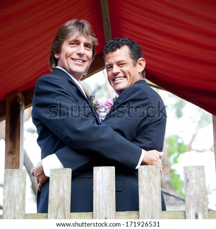Portrait of a newly married gay couple embracing on a playground in the park.   - stock photo