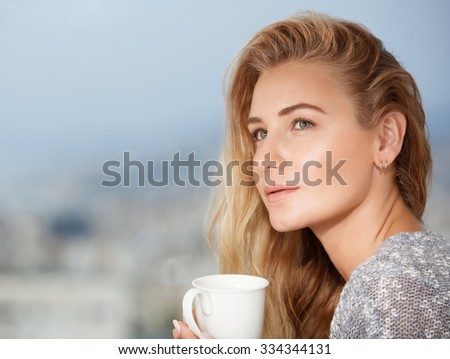 Portrait of a nice calm blond female drinking tea on the outdoors terrace, having breakfast at home, feeling morning pleasure and relaxation - stock photo