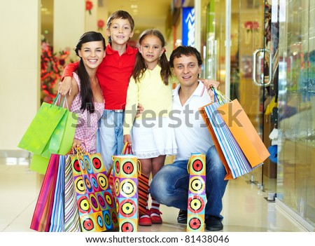 Portrait of a nice family of four with shopping bags looking at camera and smiling - stock photo
