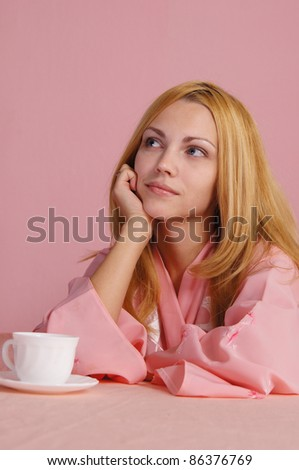 portrait of a nice girl in pink at table - stock photo
