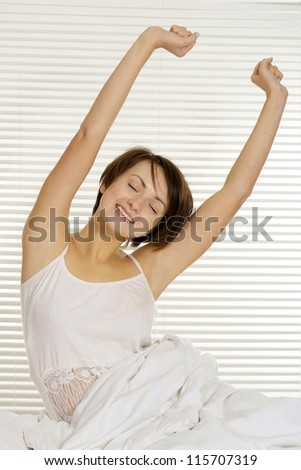 portrait of a nice girl lying in bed on a light - stock photo