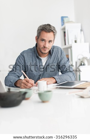 Portrait of a nice grey hair man with beard, working at home on some project, he is sitting at a white table, looking at camera while drawing plans on papers with tea in front of him. Focus on the man - stock photo