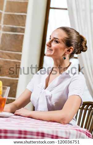 portrait of a nice lady in a restaurant, sitting with one cocktail at the table and waiting