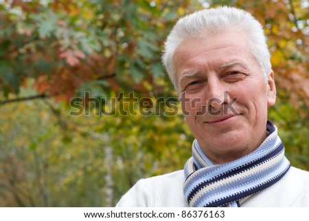 portrait of a nice old man posing at nature