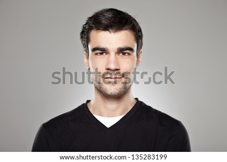 Portrait of a normal boy over grey background / Attractive young man in studio looking at camera