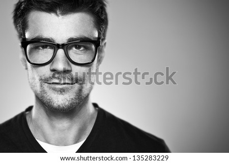 Portrait of a normal boy with rimmed glasses / Attractive young man in studio looking at camera