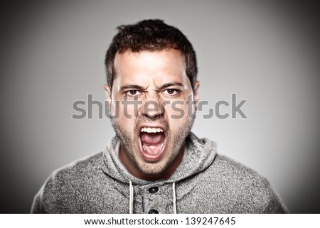 Portrait of a normal man looking furious./ Young man screaming over grey background. - stock photo