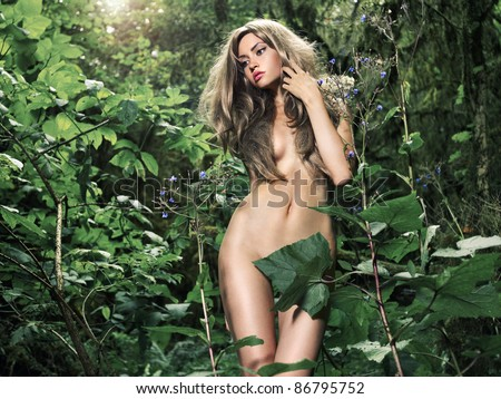 Portrait of a nude elegant lady in a green rainforest - stock photo