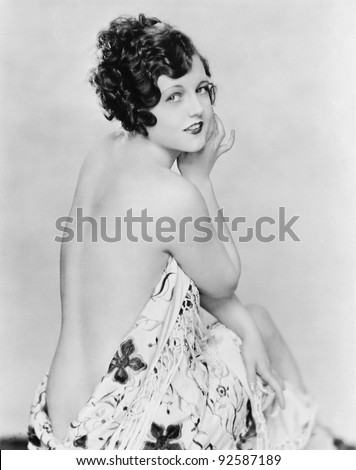 Portrait of a nude young woman draped in a sheet - stock photo