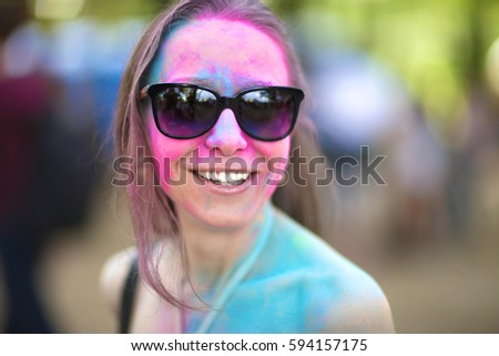 Portrait of a painted woman in sunglasses at the festival of Holi colors.