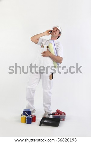 Portrait of a painter with mobile phone and plans on white background - stock photo