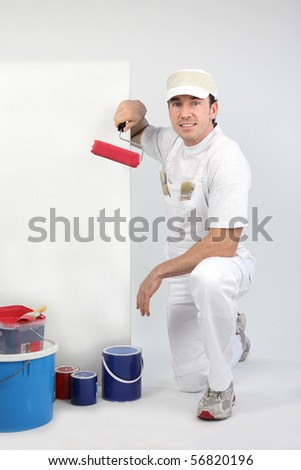 Portrait of a painter with roller brush on white background - stock photo