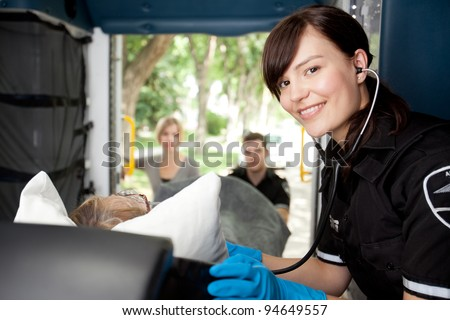 Portrait of a paramedic listening to heart rate of patient in ambulance - stock photo