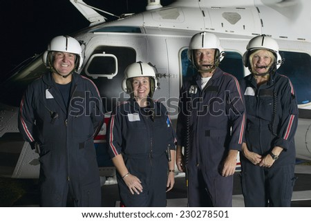 Portrait of a paramedics team smiling for the camera beside their rescue helicopter - stock photo
