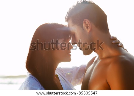 portrait of a  passionate couple in love  kissing and embracing between  backlit - stock photo