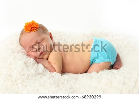 Portrait of a peaceful sleeping newborn baby girl lying on a white blanket, wearing a blue diaper cover and an orange flower headband - stock photo