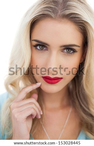Portrait of a pensive blonde woman in blue dress looking at camera on white background