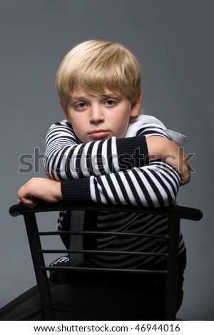 portrait of a pensive boy in a striped sweater, sitting on a chair on a gray background - stock photo