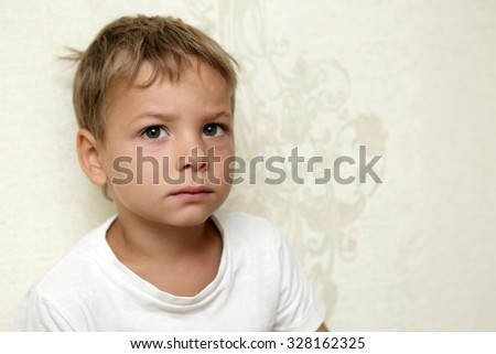 Portrait of a pensive boy on the wall background - stock photo