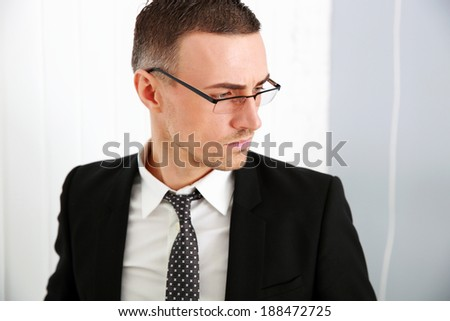 Portrait of a pensive businessman in glasses at office - stock photo