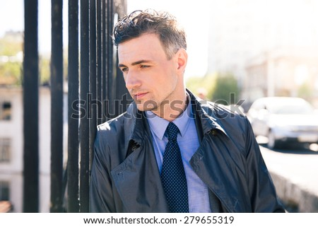 Portrait of a pensive businessman looking away. Standing outdoors - stock photo