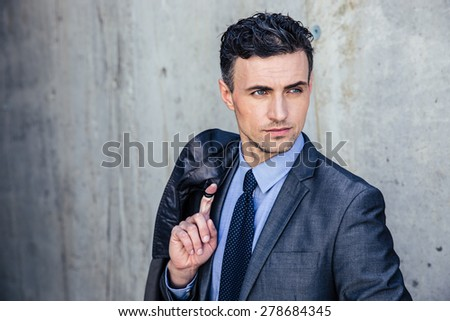 Portrait of a pensive businessman standing over concrete wall and looking away - stock photo