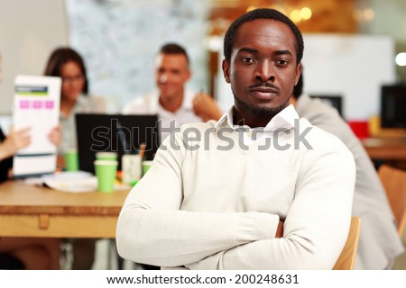 Portrait of a pensive businessman with arms folded sitting in front of colleagues - stock photo