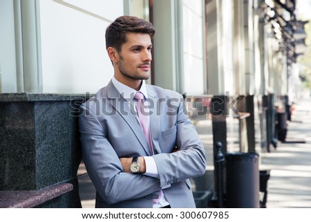 Portrait of a pensive businessman with arms folded standing outdoors in the city - stock photo