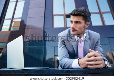 Portrait of a pensive businessman with laptop computer outdoors. Looking away - stock photo