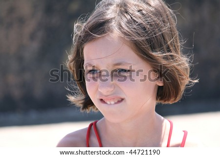 portrait of a pensive child biting her lip outdoors - stock photo