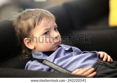 Portrait of a pensive child on the sofa - stock photo