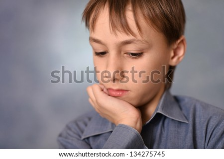 portrait of a pensive little boy over a gray background - stock photo