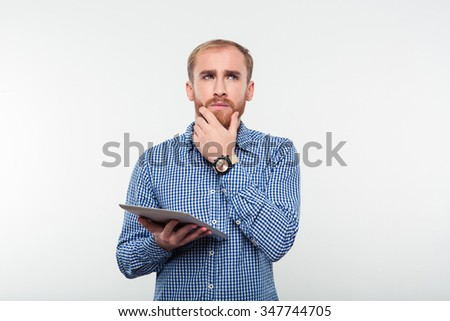 Portrait of a pensive man holding tablet computer and looking up isolated on a white background - stock photo
