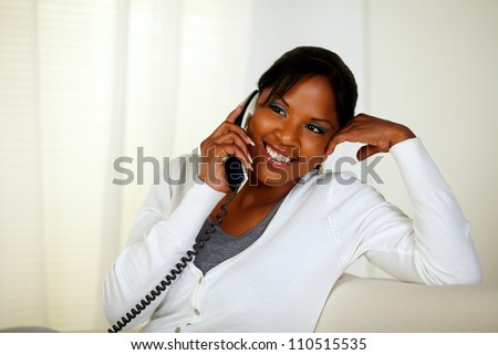 Portrait of a pensive pretty young woman conversing on phone while sitting on sofa at home indoor - stock photo