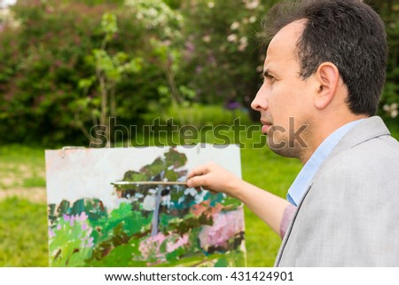 Portrait of a pensive professional painter painting in a forest and holding a paintbrush standing in front of his easel - stock photo